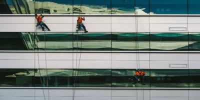 3 mænd hænger på bygning og vasker vinduer