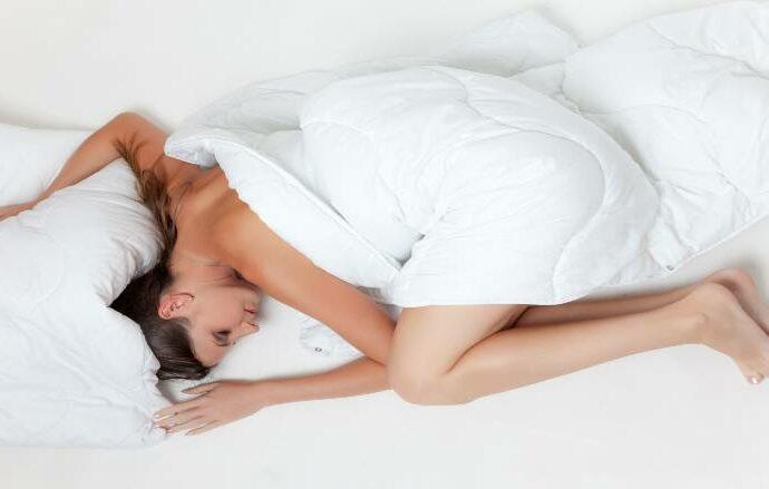Kvinder ligger alene i seng og sover